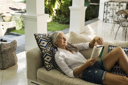 Attractive senior woman relaxing on couch, reading a book - SBOF00935