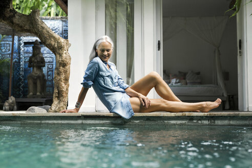 Beautiful senior woman relaxing at pool in front of her house - SBOF00944