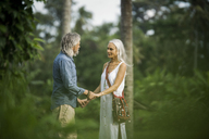 Affectionate senior couple holding hands in tropical landscape with palm trees - SBOF00959