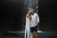 Affectionate senior couple standing in front of tropical waterfall - SBOF00962