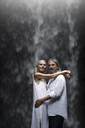 Handsome senior couple hugging in front of tropical waterfall - SBOF00965