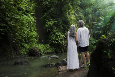 Handsome senior couple in tropical waterfall - SBOF00974