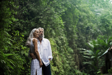 Affectionate handsome senior couple in tropical jungle - SBOF00977