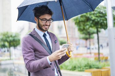 Fashionable businessman with umbrella checking his cell phone in the city - BSZF00098