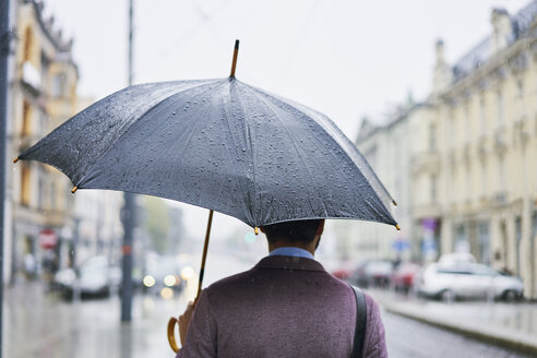 Back view of businessman in the city with umbrella on a rainy day - BSZF00101