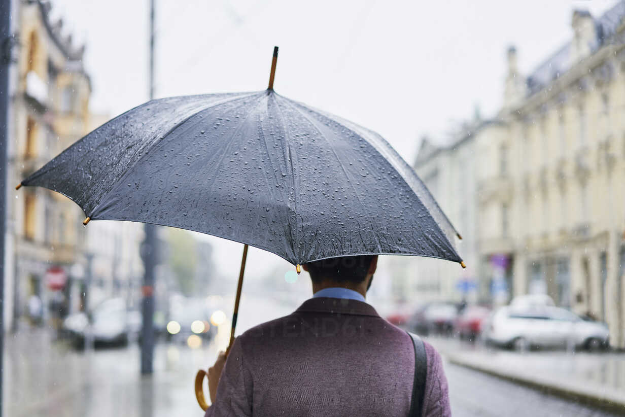 Back view of businessman in the city with umbrella on a rainy day - BSZF00101 - Bartek Szewczyk/Westend61