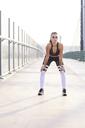 Female runner having break during city workout - BSZF00109