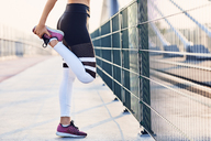 Close-up of woman stretching legs after running - BSZF00112