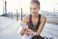 Happy woman with smartphone after urban workout - BSZF00115