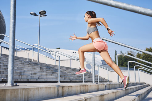 Fit young woman running on stairs - BSZF00124