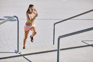 Fit young woman running on stairs - BSZF00127