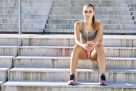 Fit woman sitting on stairs with smartphone and earphones - BSZF00130