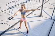 Young woman doing kettlebell swing exercise outdoors - BSZF00136