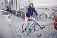 Blond woman riding a bike in the city - PNEF00374