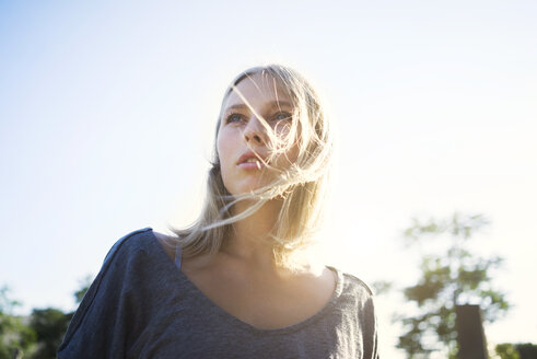 Portrait of blond young woman with blowing hair at backlight - KNSF03137