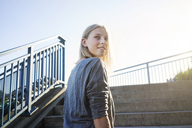 Portrait of blond young woman in front of staircase - KNSF03143