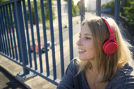 Portrait of smiling young woman listening music with headphones - KNSF03146