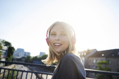 Portrait of smiling young woman at backlight listening music with headphones - KNSF03149