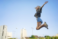 Happy young woman jumping in the air - KNSF03155