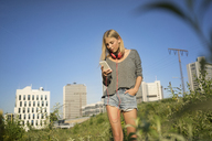 Young woman looking at cell phone - KNSF03158