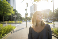 Portrait of laughing young woman at backlight - KNSF03164
