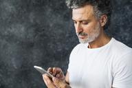 Mature man using smartphone, sending text messages - HAPF02462