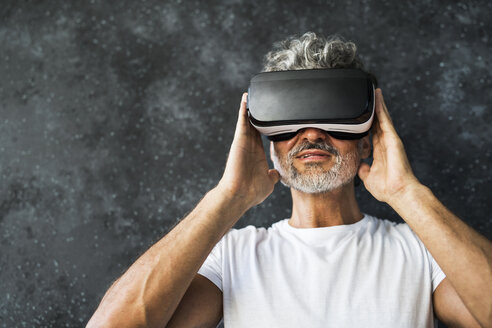 Mature man looking through VR glasses - HAPF02468