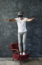Mature man looking through VR glasses, balancing on armchair - HAPF02471