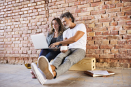 Businessman and woman sitting in a loft, using laptop, founding a start-up company - HAPF02474