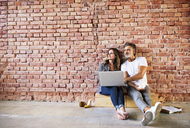 Businessman and woman sitting in a loft, using laptop, founding a start-up company - HAPF02477