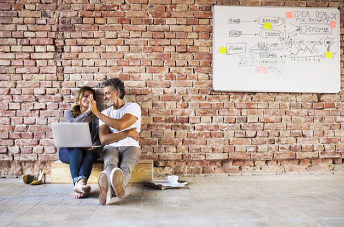Businessman and woman sitting in a loft, giving high five, founding a start-up company - HAPF02480