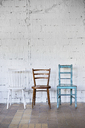 Empty chairs against white brick wall - HAPF02501
