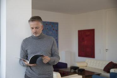 Businessman reading magazine in apartment - SUF00374