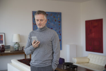 Businessman with smartphone in apartment - SUF00377