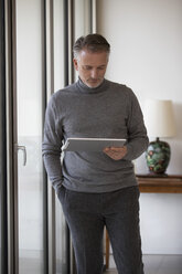 Businessman using tablet in apartment - SUF00380