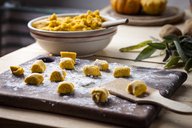 Preparing pumpkin gnocchi, rolling on wooden board - SBDF03393
