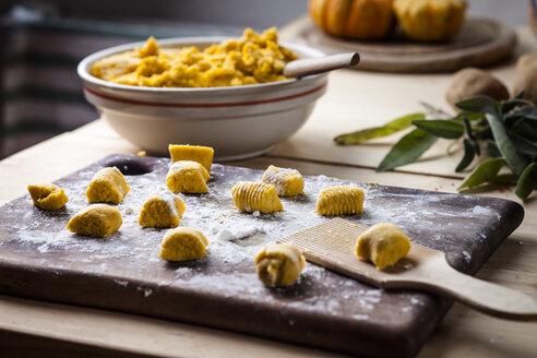 Preparing pumpkin gnocchi, rolling on wooden board - SBDF03393