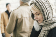 Smiling blond woman covered with knitted scarf - KMKF00088