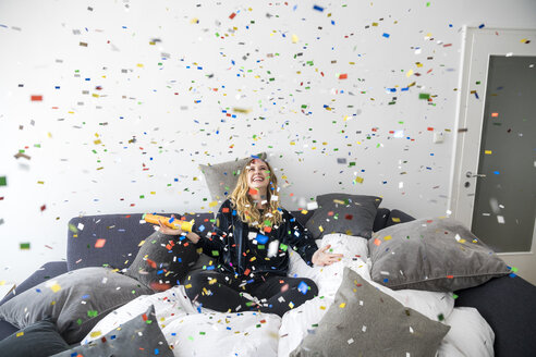 Laughing young woman having fun with flying confetti at home - FMKF04648