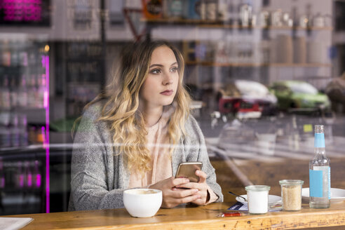 Portrait of pensive young woman in a coffee shop looking through window - FMKF04657