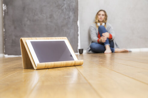 Tablet on tablet stand on the floor with young woman sitting in the background - FMKF04678