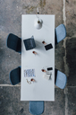 Conference table seen from above, turkish tea, prayer beads, tablet, smartphone, laptop and notebook - JOSF02077