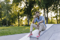 Smiling young man on cell phone sitting in skatepark - KNSF03185