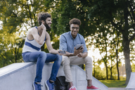Two happy friends sitting in a skatepark with mobile devices - KNSF03194