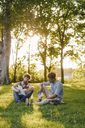 Two friends sitting in a park with mobile device and papers - KNSF03200