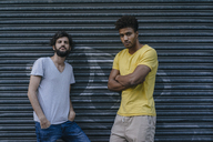 Two friends standing at roller shutter in the city - KNSF03203