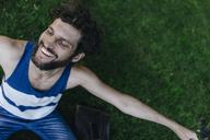 Happy man sitting on a meadow in park - KNSF03233