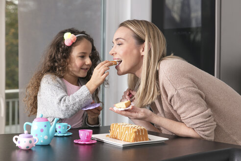 Mother and little daughter little  playing together with doll's china set - GDF01178