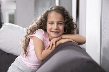 Portrait of smiling little girl with tooth gap on the couch - GDF01181