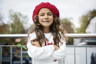 Portrait of smiling little girl with tooth gap wearing red woolly hat - GDF01184